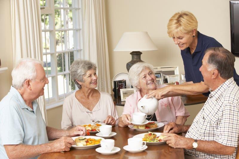 Grupo de pares superiores que aprecia a refeição junto na casa do cuidado com ajuda home imagens de stock