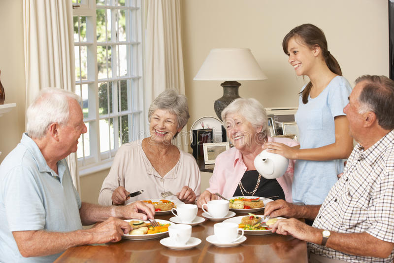 Grupo de pares superiores que aprecia a refeição junto na casa do cuidado com ajudante adolescente fotos de stock royalty free