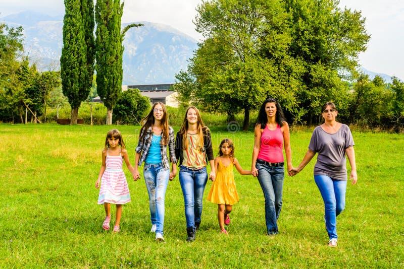 Grupo de passeio de passeio dos amigos fêmeas através do parque imagens de stock royalty free