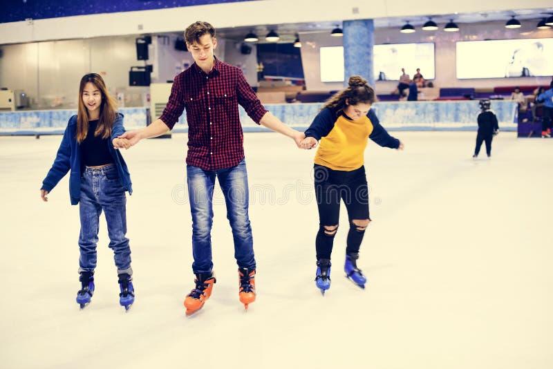 Grupo de patinagem no gelo adolescente dos amigos em uma pista de gelo imagens de stock