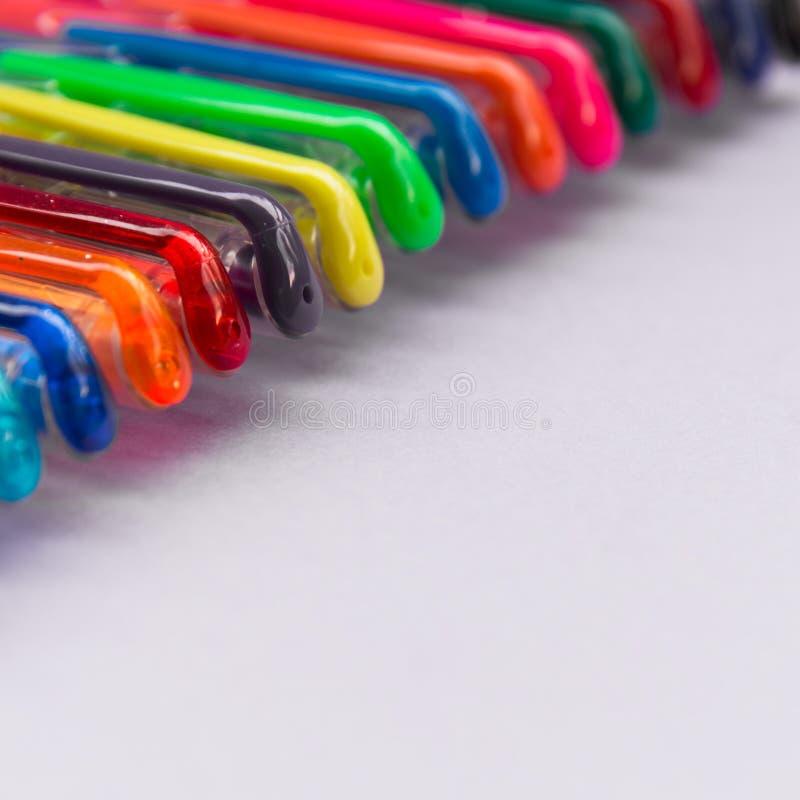 Grupo de penas do gel de várias cores com fundo lilás fotos de stock royalty free