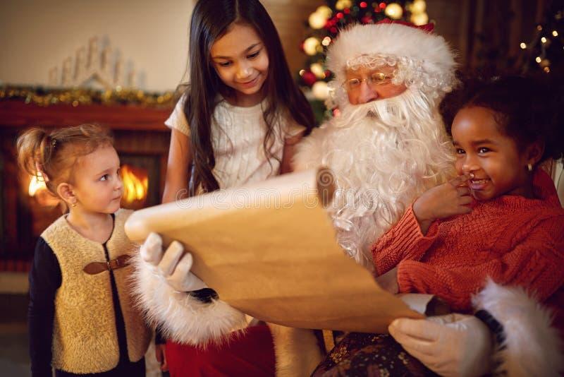 Grupo de pequeñas muchachas étnicas multi que miran en Santa Claus con w fotografía de archivo libre de regalías