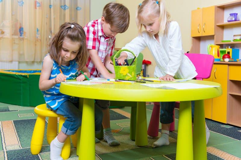 Grupo de pequeño jugar lindo de los niños del prescool imagen de archivo