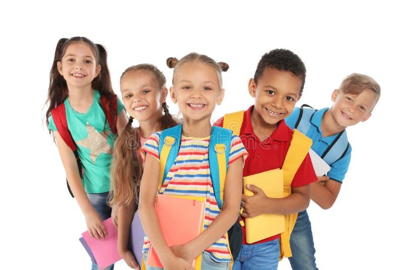 Grupo de pequeños niños con las mochilas foto de archivo