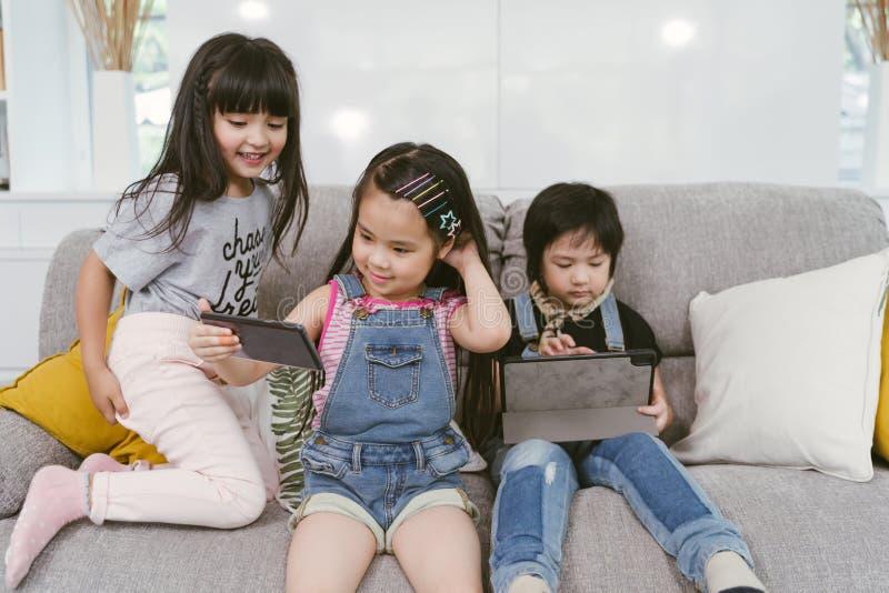 Grupo de pequeños niños que miran la historieta de la película de la película junto en la tableta y el teléfono digitales Ni?os q imagenes de archivo