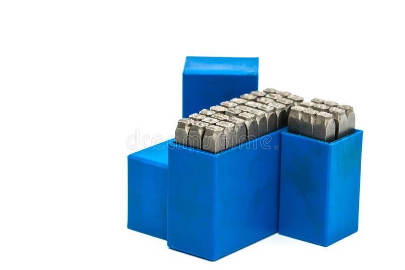 Grupo de perfurador do alfabeto e do número do selo do metal na caixa plástica azul isolada no fundo branco fotografia de stock royalty free