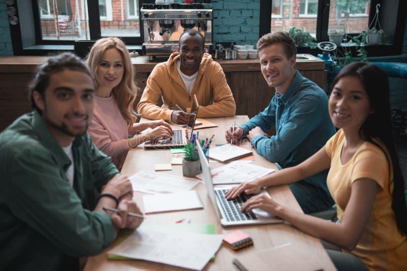 Grupo de personas alegre que trabaja en el escritorio fotografía de archivo libre de regalías