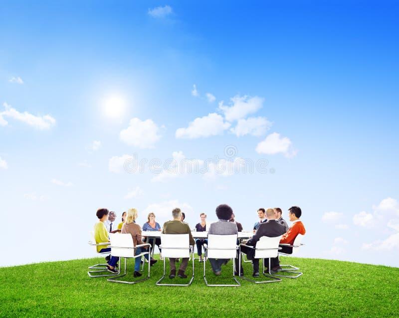 Grupo de personas alrededor de la mesa de reuniones imágenes de archivo libres de regalías