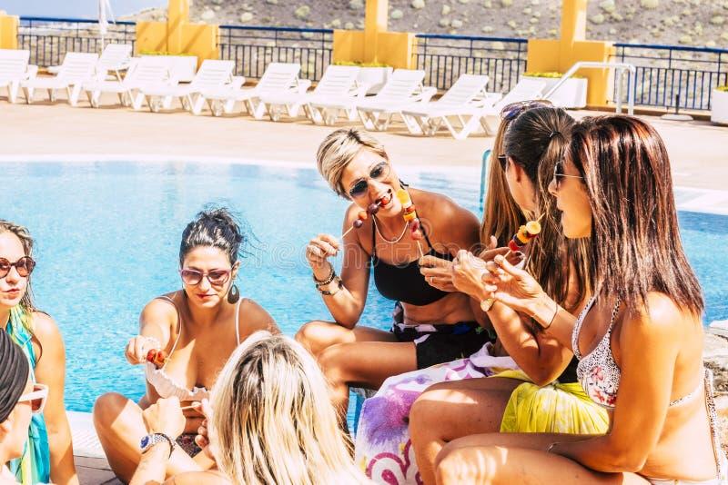 Grupo de personas con forma de vida sana que come la fruta junta cerca de una piscina azul - concepto de vacaciones de verano y d foto de archivo