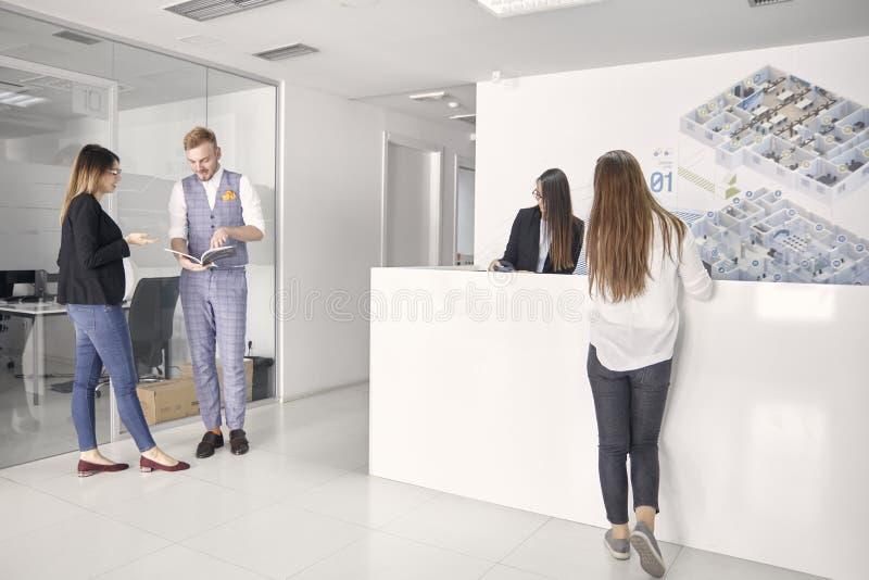 Grupo de personas, cuatro empresarios jovenes, encontrándose en el vestíbulo moderno de la oficina, mirando los papeles fotografía de archivo
