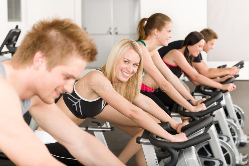 Grupo de personas de la aptitud en la bici de la gimnasia imagen de archivo