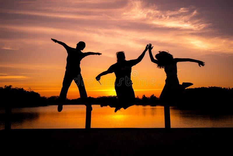 Grupo de personas del retrato de la silueta que salta con puesta del sol fotografía de archivo libre de regalías