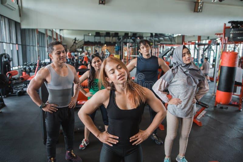 Grupo de personas delantero de la mirada en el gimnasio que estira para calentar imagen de archivo libre de regalías