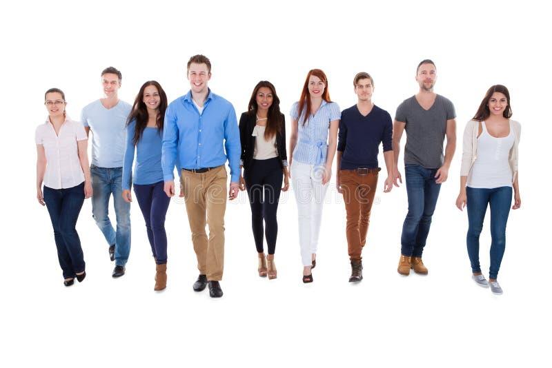 Grupo de personas diverso que camina hacia cámara foto de archivo