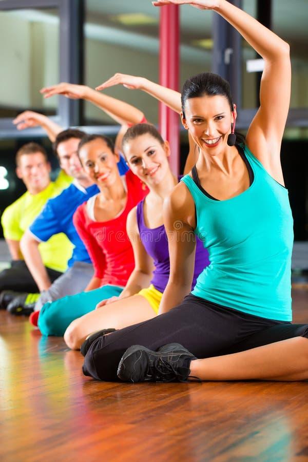 Grupo de personas e instructor en estirar del gimnasio imagenes de archivo