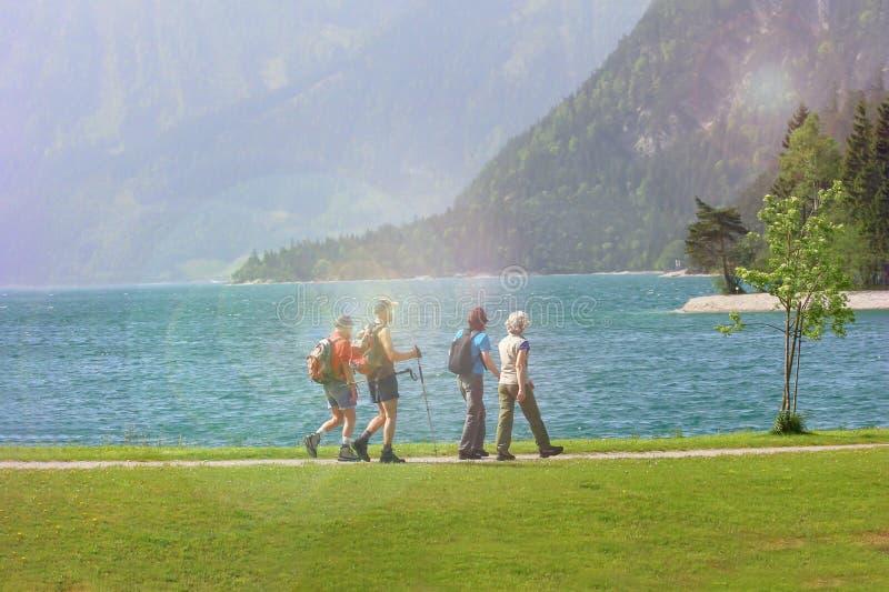 Grupo de personas en caminar nórdico de la naturaleza efecto del resplandor del sol imagenes de archivo