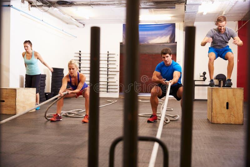 Grupo de personas en el entrenamiento del circuito del gimnasio imagen de archivo libre de regalías