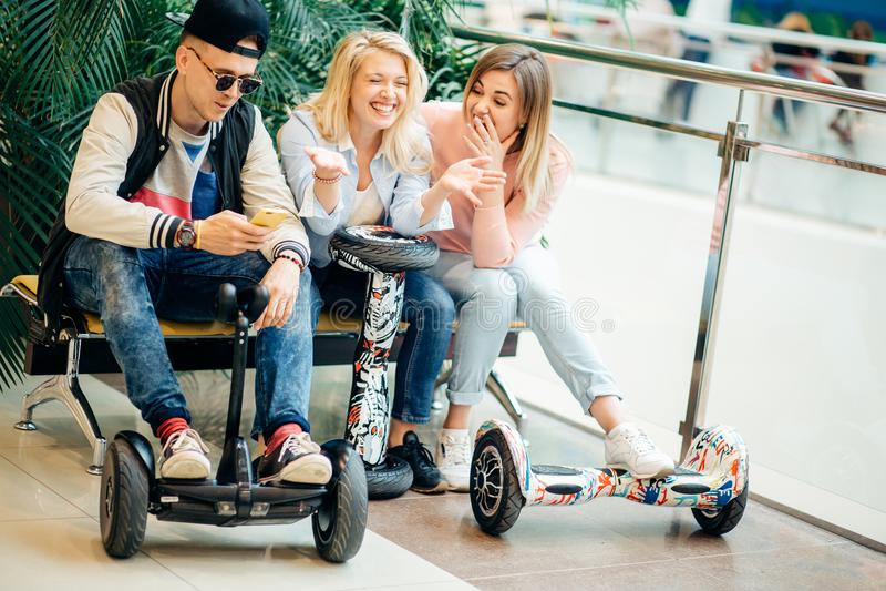 Grupo de personas en el hoverboard eléctrico de la vespa que se sienta en el banco y que usa el teléfono imagenes de archivo