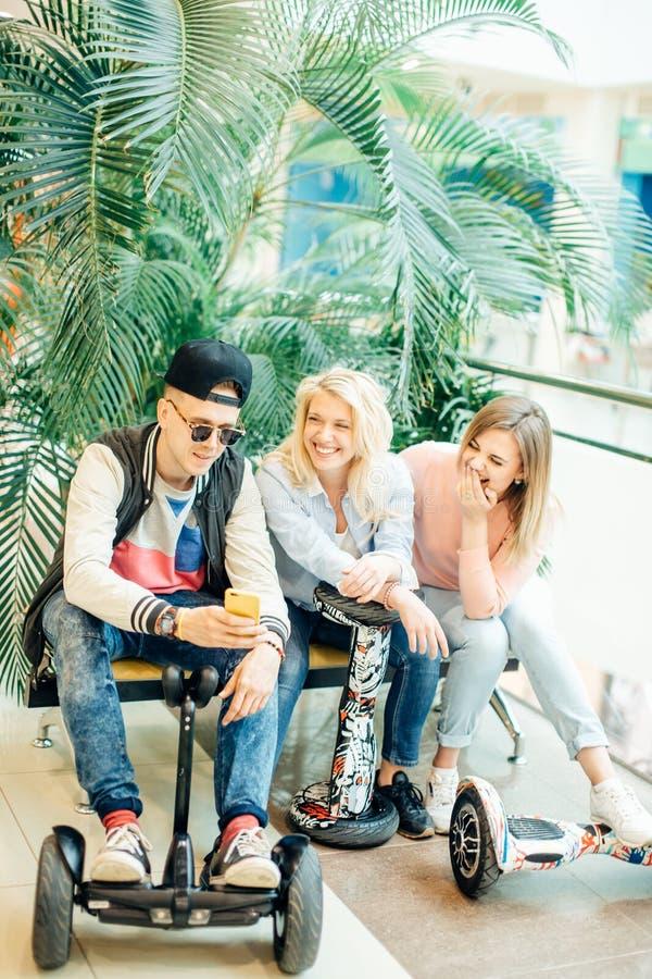 Grupo de personas en el hoverboard eléctrico de la vespa que se sienta en el banco y que usa el teléfono fotografía de archivo