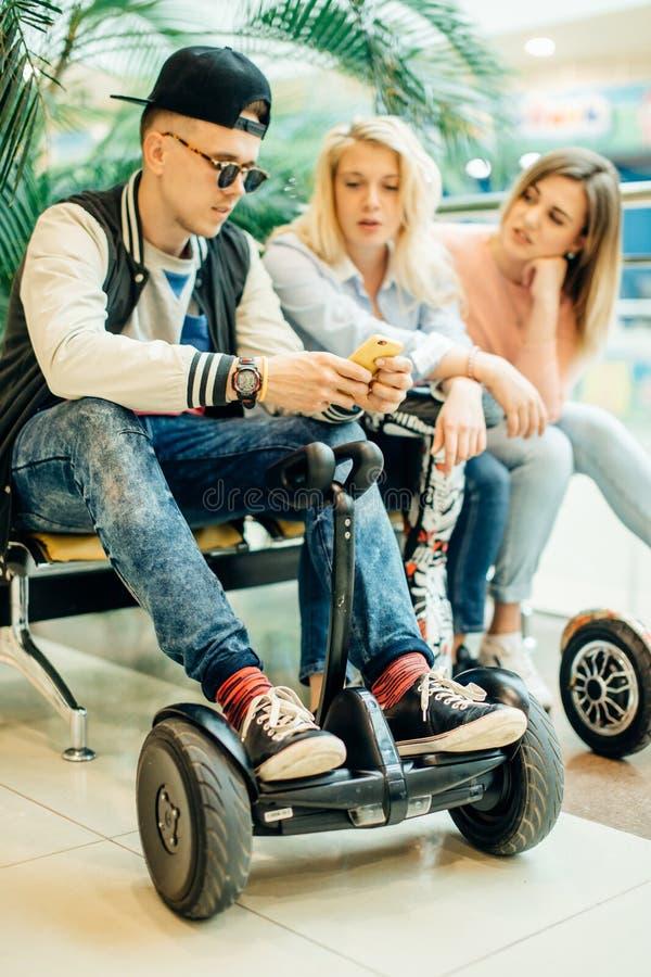Grupo de personas en el hoverboard eléctrico de la vespa que se sienta en el banco y que usa el teléfono fotos de archivo libres de regalías