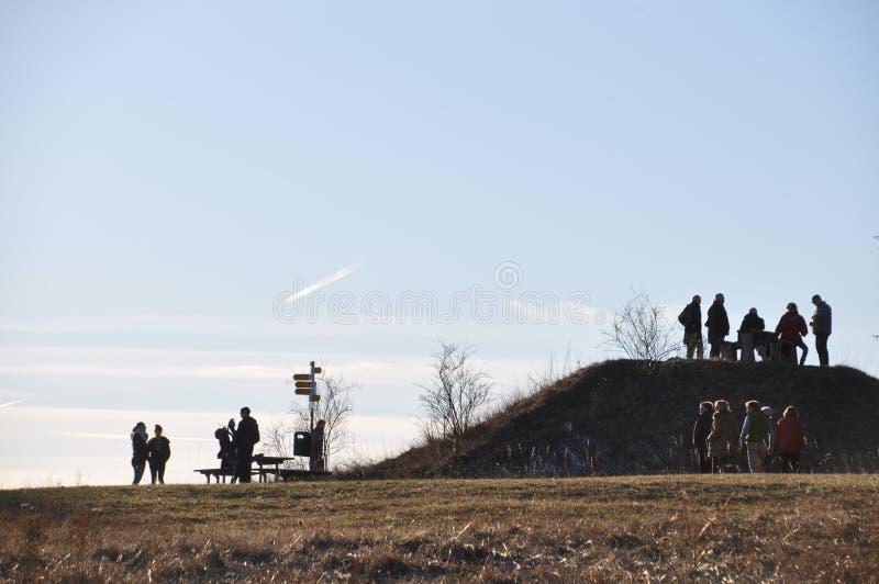 Grupo de personas en el poste de la perspectiva en el top de la monta?a fotografía de archivo