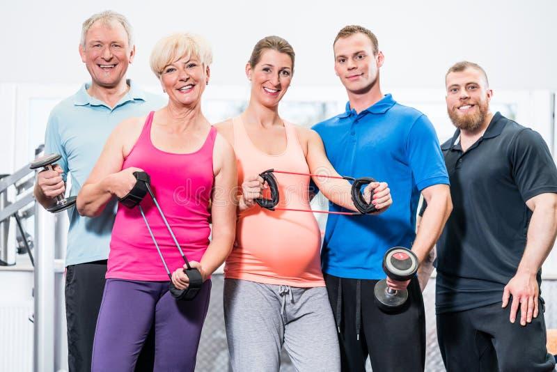 Grupo de personas en gimnasio con las bandas y las pesas de gimnasia del estiramiento imagenes de archivo