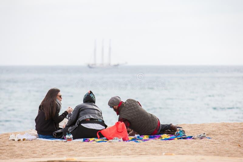 Grupo de personas en la playa de Barceloneta del La en invierno fotografía de archivo