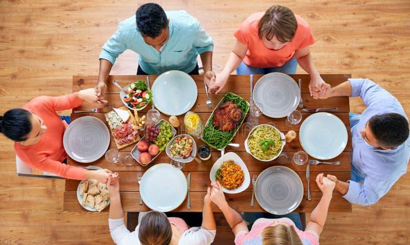 Grupo de personas en la tabla que ruega antes de comida fotos de archivo