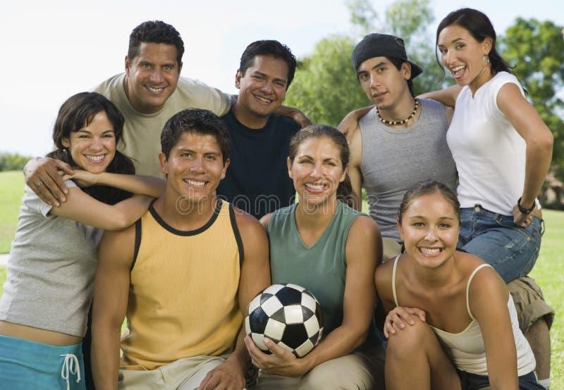 Grupo de personas en parque con la mujer que sostiene el balón de fútbol. imagen de archivo