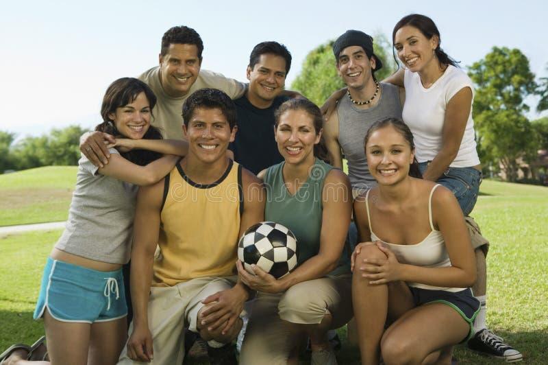 Grupo de personas en parque con la mujer que sostiene el balón de fútbol. fotos de archivo