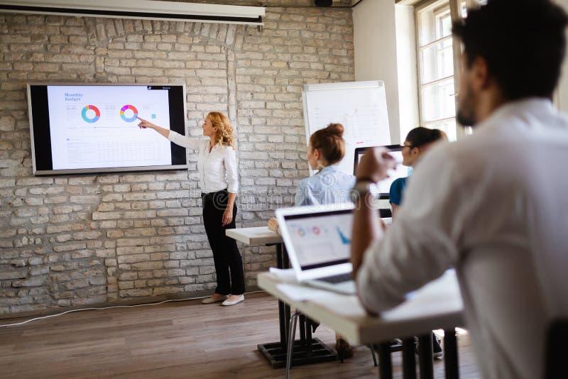 Grupo de personas feliz acertado que aprende la ingeniería y el negocio de programas informáticos durante la presentación imágenes de archivo libres de regalías