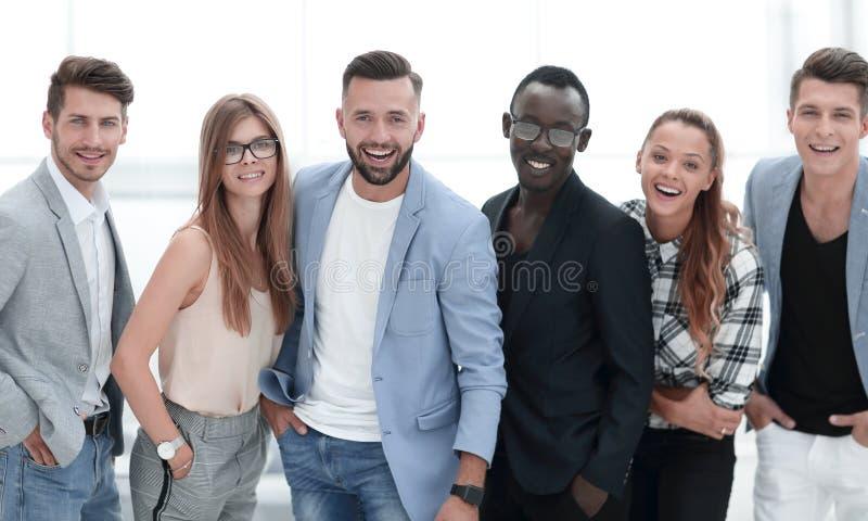Grupo de personas feliz que se coloca en fila sobre el fondo blanco imágenes de archivo libres de regalías