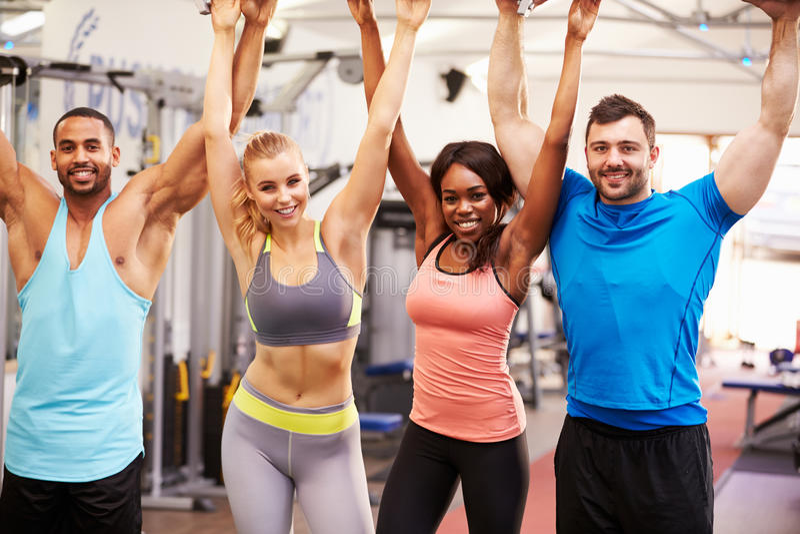 Grupo de personas feliz, sano con los brazos en el aire en un gimnasio imagenes de archivo
