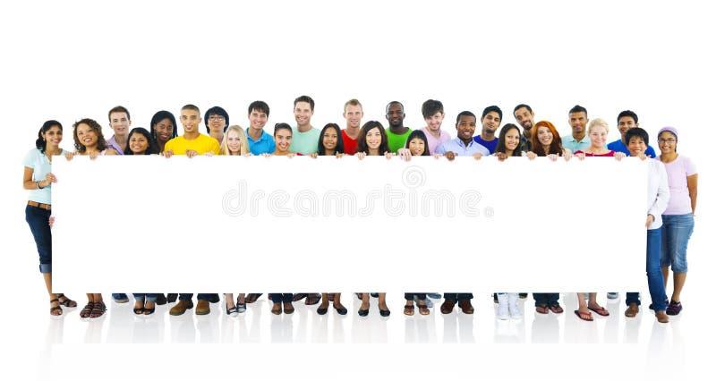 Grupo de personas grande que lleva a cabo al tablero imagen de archivo libre de regalías