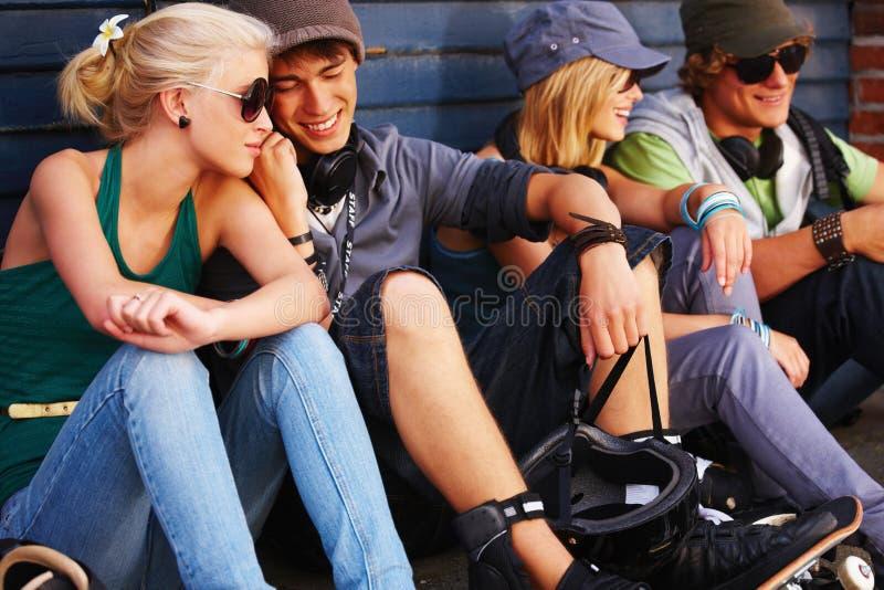 Grupo de personas joven que se sienta junto divirtiéndose imagen de archivo