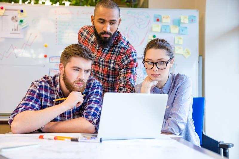 Grupo de personas multiétnico enfocado que trabaja con el ordenador portátil junto foto de archivo libre de regalías