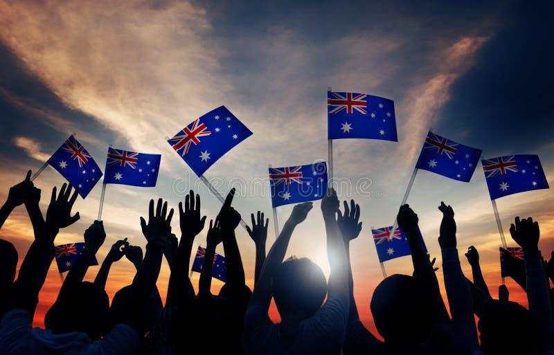 Grupo de personas que agita banderas australianas en Lit trasero fotografía de archivo libre de regalías