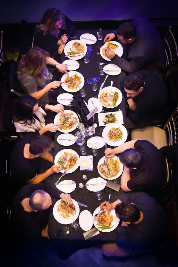 Grupo de personas que cena o que come imagen de archivo libre de regalías