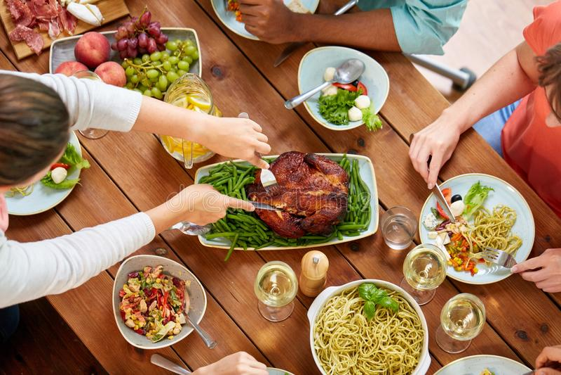Grupo de personas que come el pollo para la cena imagen de archivo