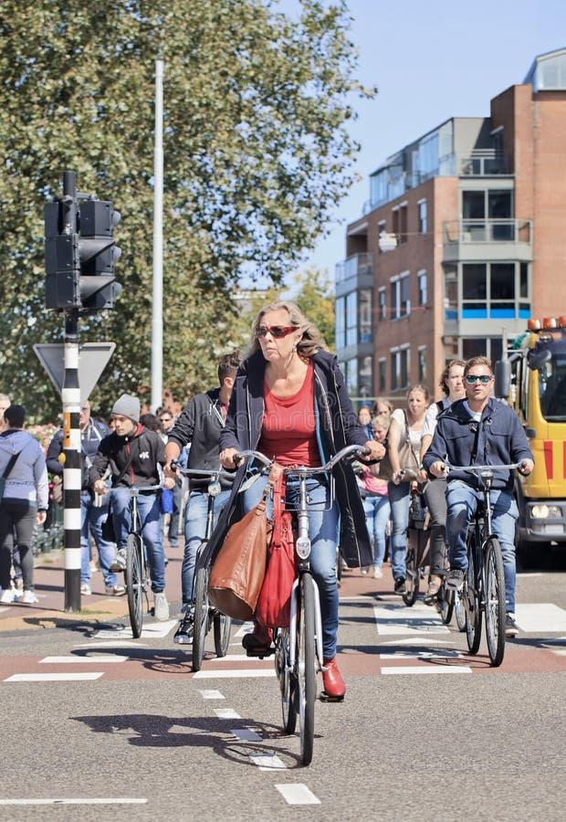 Grupo de personas que completa un ciclo en el centro de ciudad, Amsterdam, Países Bajos fotos de archivo