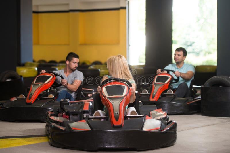 Grupo de personas que conduce la raza de Karting del kart imagen de archivo