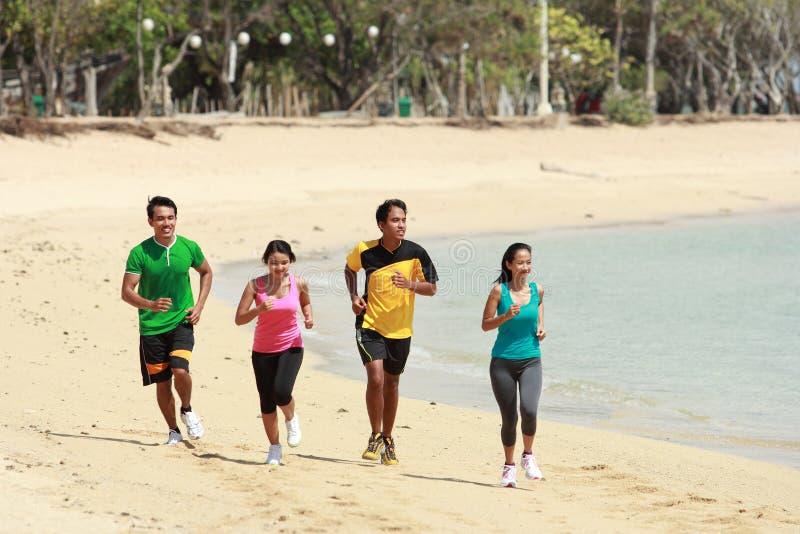 Grupo de personas que corre en la playa, concepto del deporte imagen de archivo libre de regalías