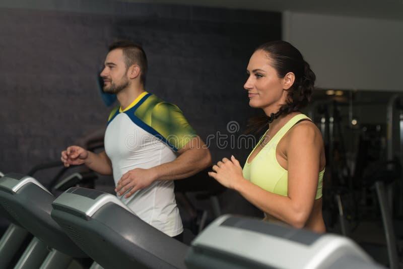 Grupo de personas que corre en las ruedas de ardilla en gimnasio imagen de archivo libre de regalías