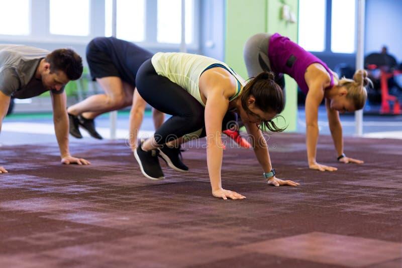 Grupo de personas que ejercita en gimnasio imagen de archivo