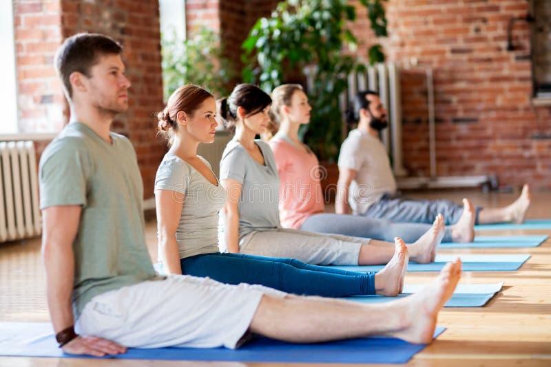 Grupo de personas que hace actitud del personal de la yoga en el estudio fotos de archivo libres de regalías