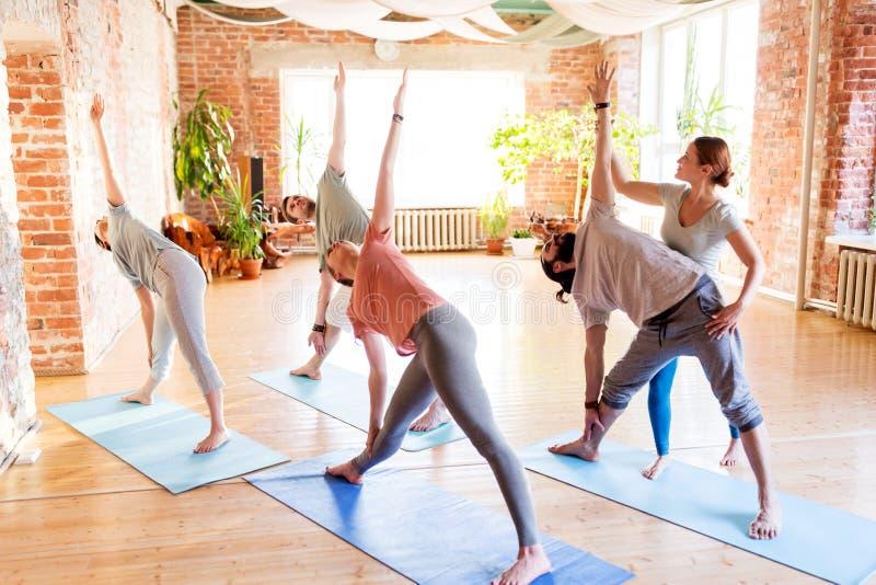 Grupo de personas que hace ejercicios de la yoga en el estudio fotografía de archivo libre de regalías