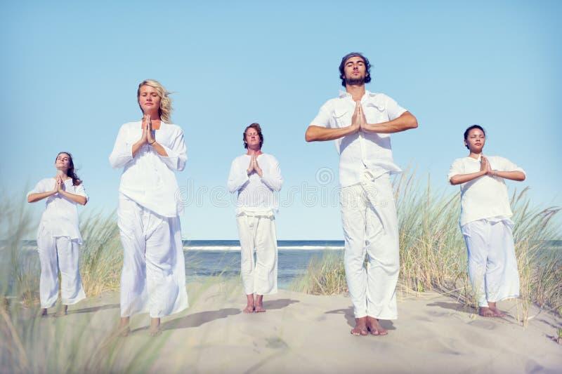 Grupo de personas que hace yoga en la playa fotos de archivo libres de regalías