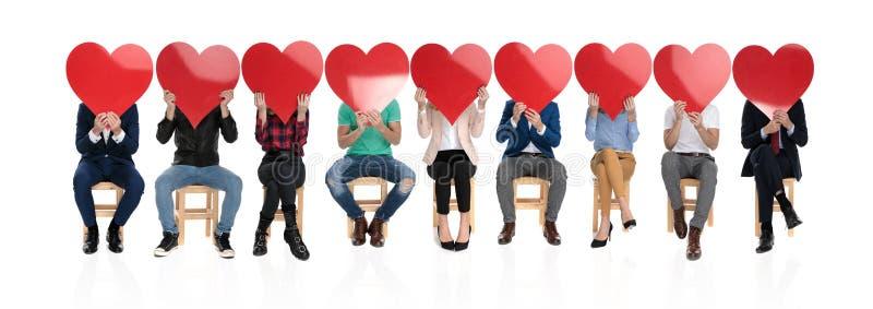 Grupo de personas que lleva a cabo corazones rojos grandes sobre sus caras foto de archivo libre de regalías