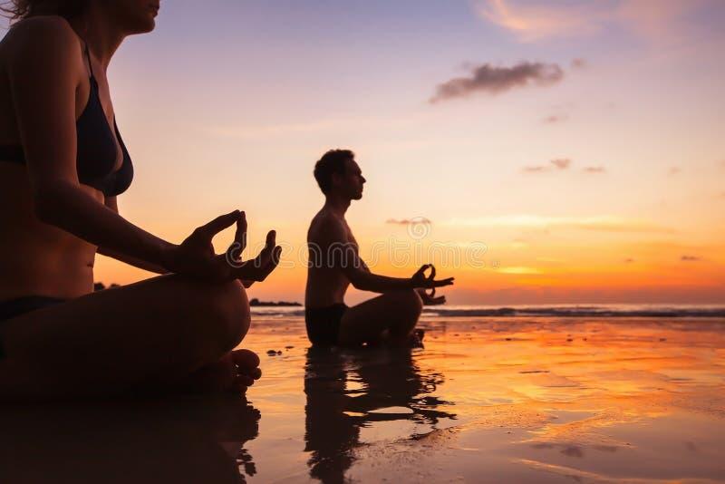 Grupo de personas que reflexiona sobre la playa, yoga fotografía de archivo libre de regalías