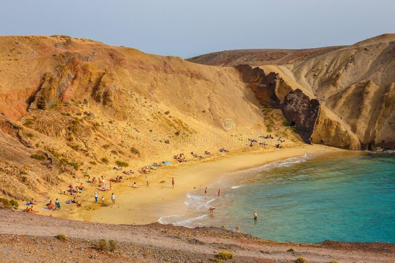 Grupo de personas que se relaja en la playa de Papagayo en la isla de Lanzarote, España fotos de archivo libres de regalías